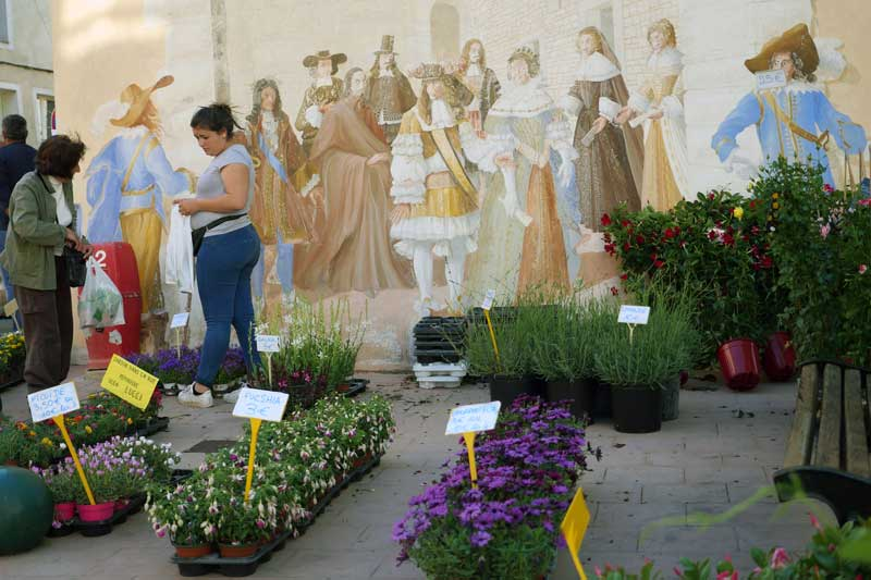 A nursery comes to Saturday market beneath another mural depicting a moment from history.